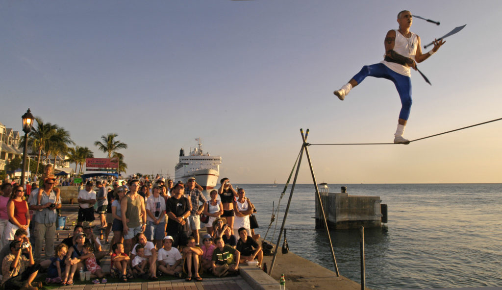 A street performer juggles on a tightrope at the sunset celebration in Key West