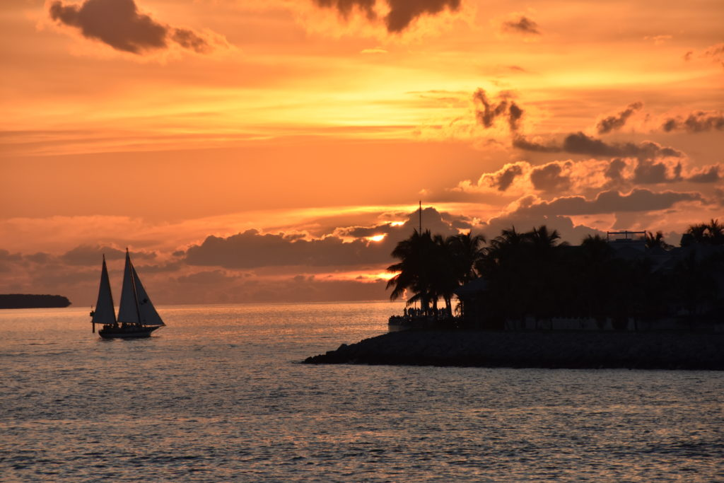the sun is setting behind a island with a sail boat sailing towards the sinking sun with a very vibrant orange and yellow sky.