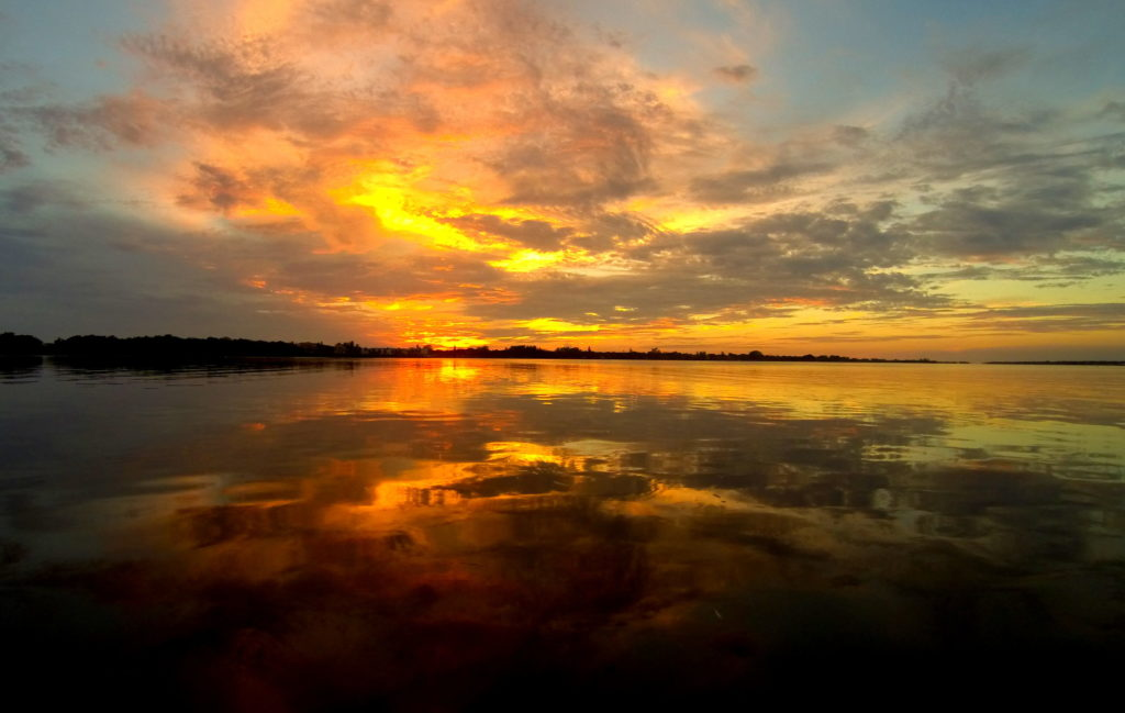 radiating orange and yellow clouds fill the sky and reflect off of the water as the as the sun sets.