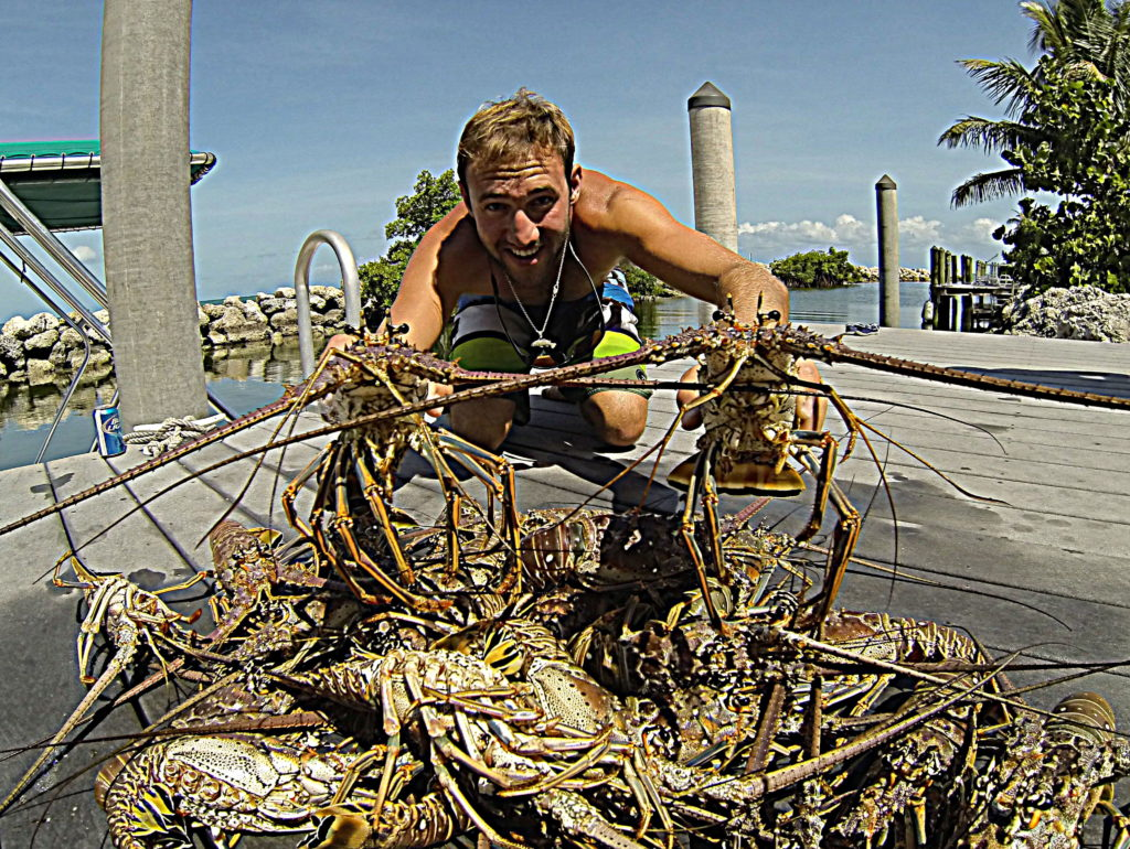 captain nick labadie poses with a pile of lobster caught while free diving in the Florida keys.