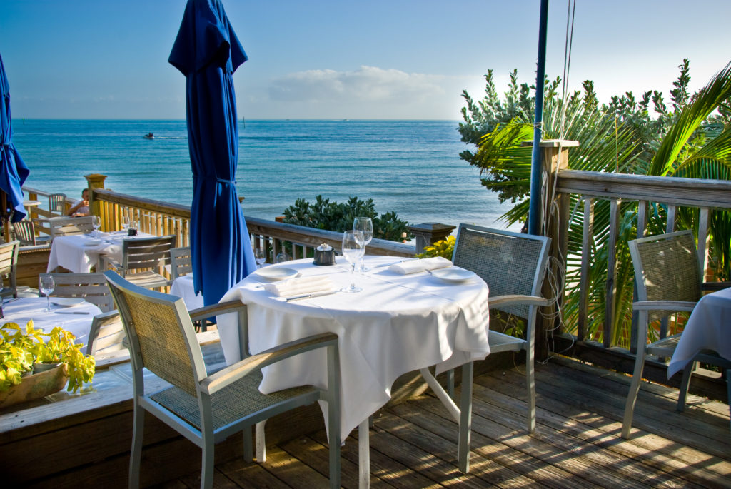 the view of the outside dining area at Louies backyard with white linen table cloth and a view right on the the Atlantic ocean