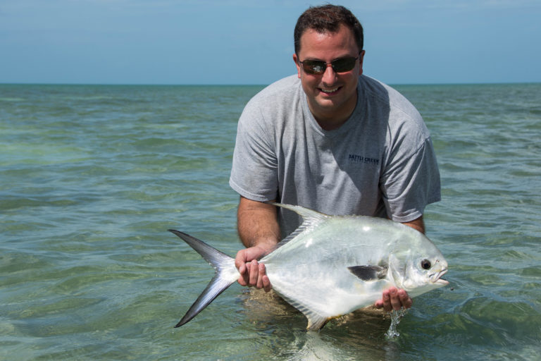 An angler is standing in the water holding a freshly caught permit off of the flats in in the Florida keys.