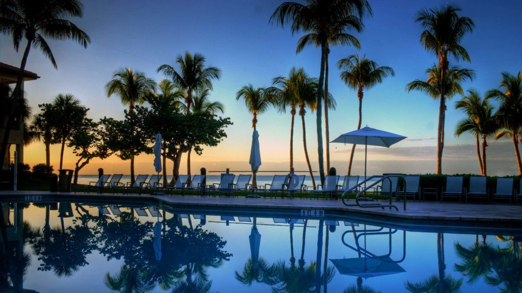 the sun goes down over the pool at the casa marina resort in key west Florida
