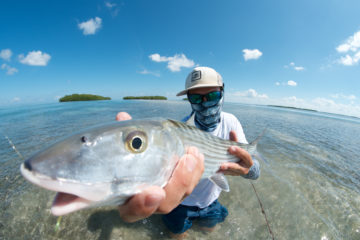 A close up picture of nick labadie holding a beautiful lower keys bonefish caught on fly on a clear backcountry flat with blue skies and mangrove islands in the background.