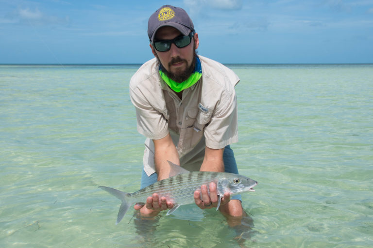 An angler is in knee deep water posing with a nice lower keys bonefish he had just sight fished off the flats.