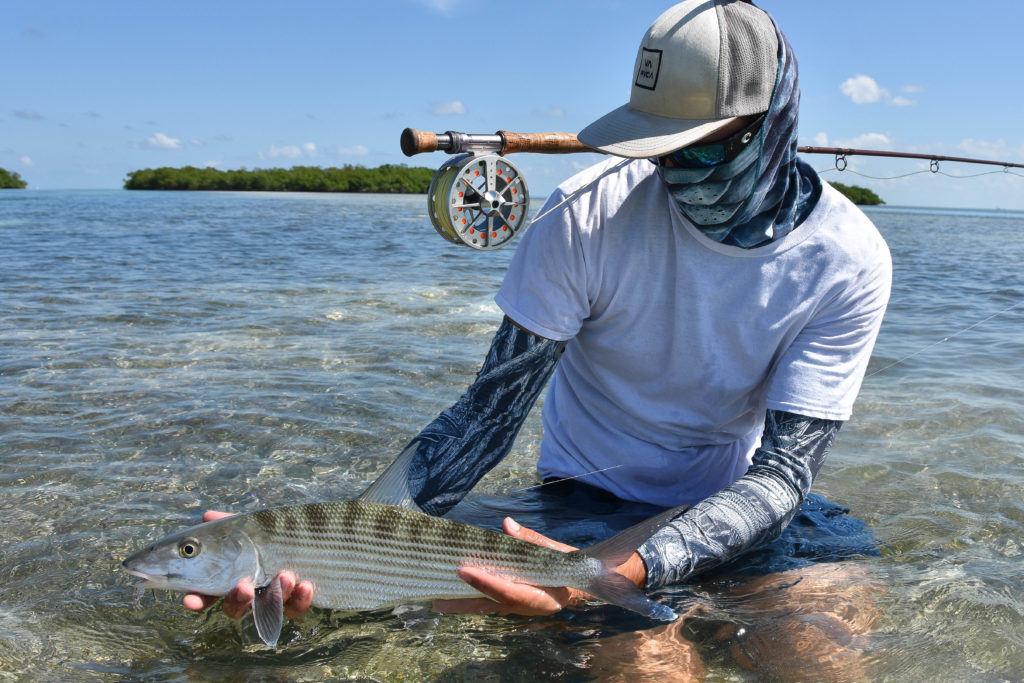 Nick Labadie is kneeling on a backcountry flat in a less than a foot of gin clear lower keys water holding a beautiful bonefish caught with a fly rod.