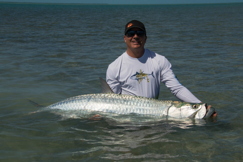 An angler is in the water holding a huge tarpon on the flats off of Key West, Florida.
