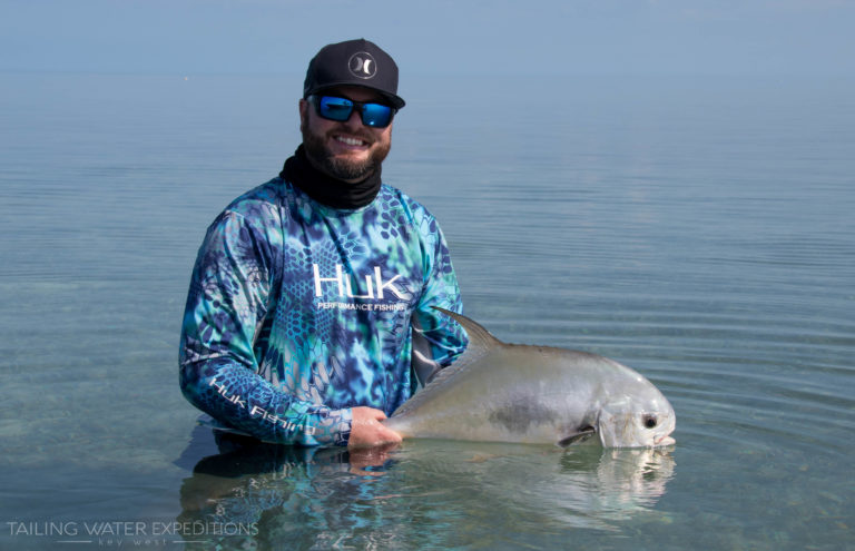 An angler gets in the water to take a picture with his first permit!