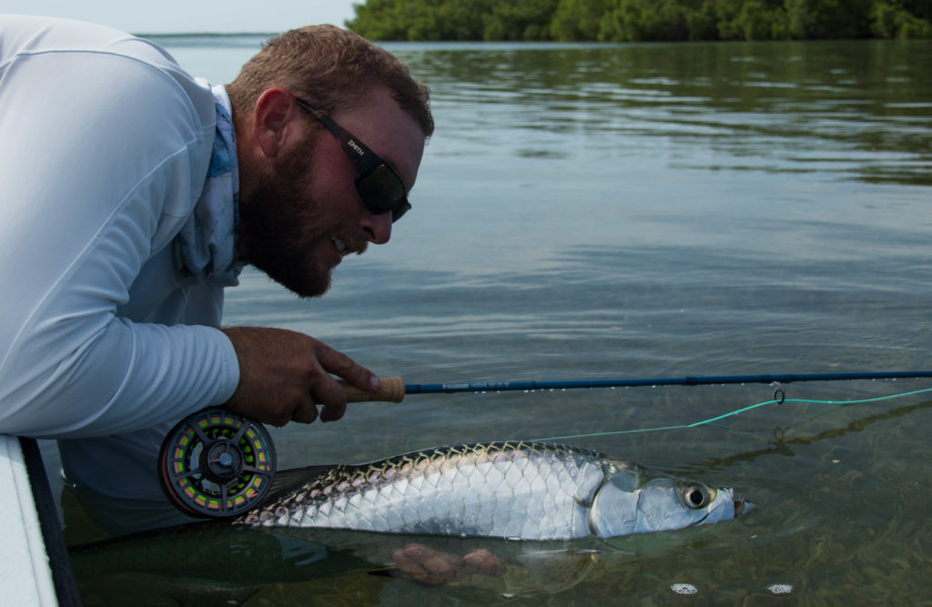 Capt. Kyle Kelso holds up a nice juvenile tarpon caught on fly
